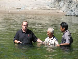 Missionary Terry Reed and Vicente baptizing Vicente's grandfather.